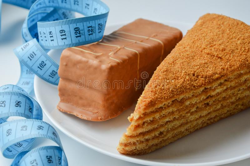 Two delicious cream cakes on a white plate. delicious sweets. blue ribbon meter. the waist measurement. diet, weight loss. Two delicious cream cakes on a white royalty free stock photo