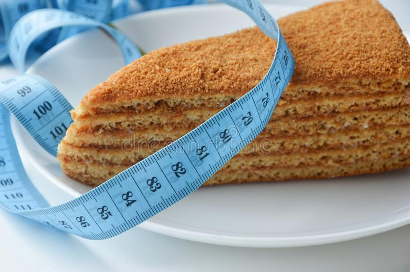 Two delicious cream cakes on a white plate. delicious sweets. blue ribbon meter. the waist measurement. diet, weight loss. Two delicious cream cakes on a white stock images