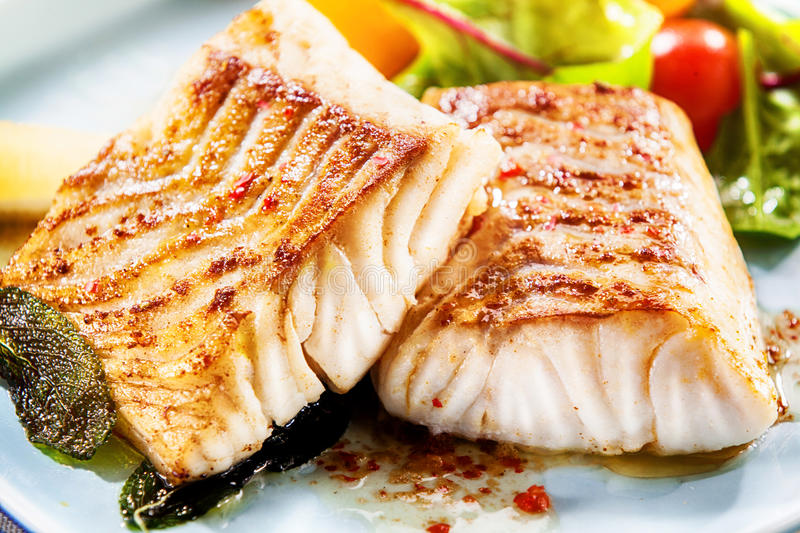 Two delicious fillets of marinated pollock. Two delicious fillets of marinated grilled or oven baked pollock or coalfish served with a fresh salad, close up view royalty free stock image