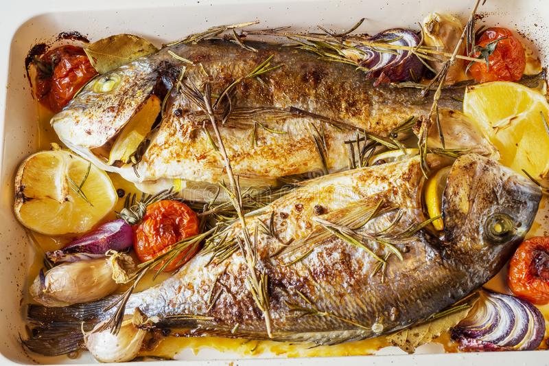 Two delicious whole baked fish. Baked dorado with lemon, onions, rosemary, cherry tomatoes, and spices on a wooden background. Delicious roasted dorado on oven stock photography