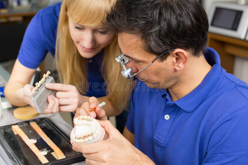 Two dental technicians choosing the right colour for dental porcelain royalty free stock photo