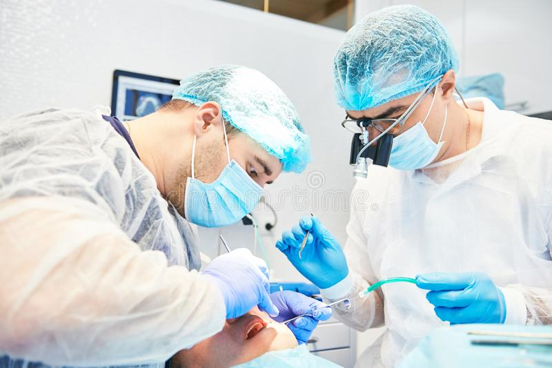 Two dentist perform dental operation on a patient royalty free stock image