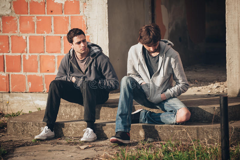 Two depressed and sad young buddies friends thinking about problems stock image
