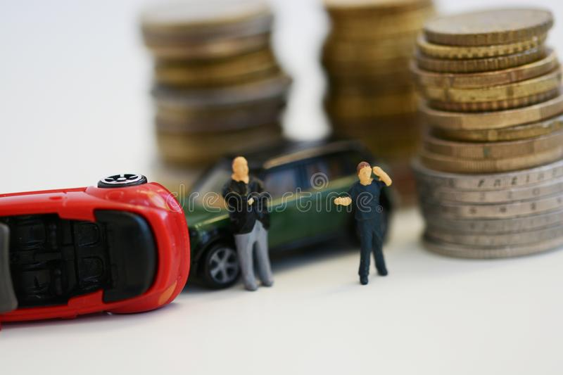 Two desperate men near toy cars involved in accident, conceptual image with miniatures and figurines isolated on white background stock image