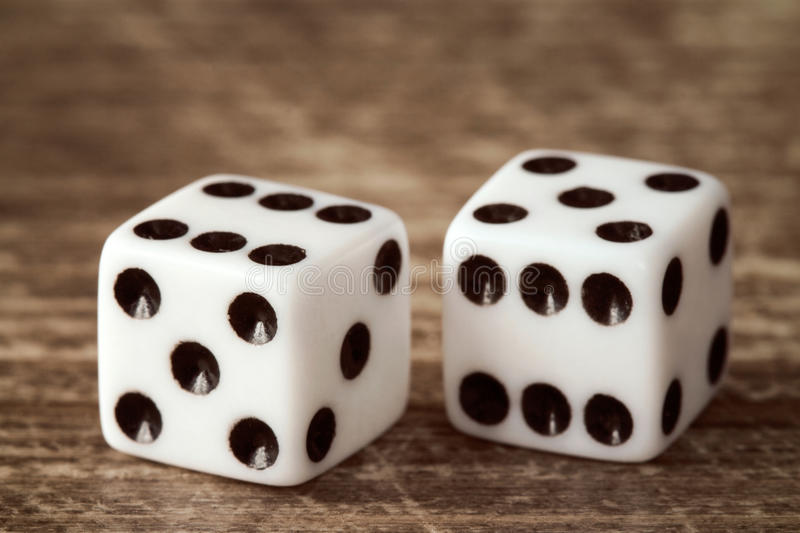 Two dice on dark wooden table stock images