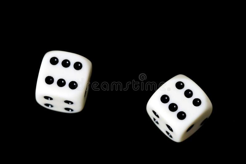Two dice showung six on a black backround royalty free stock images