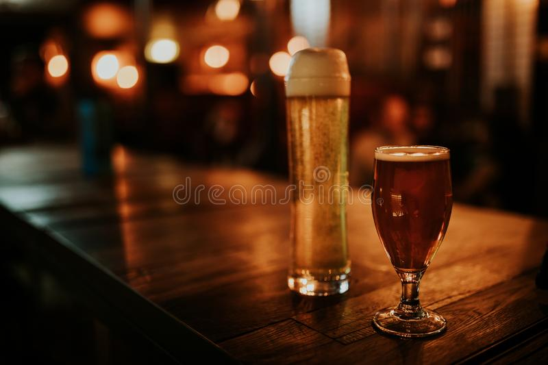 Two different beers on a wooden table, with pub lights in the background at night. And left copy space stock photo