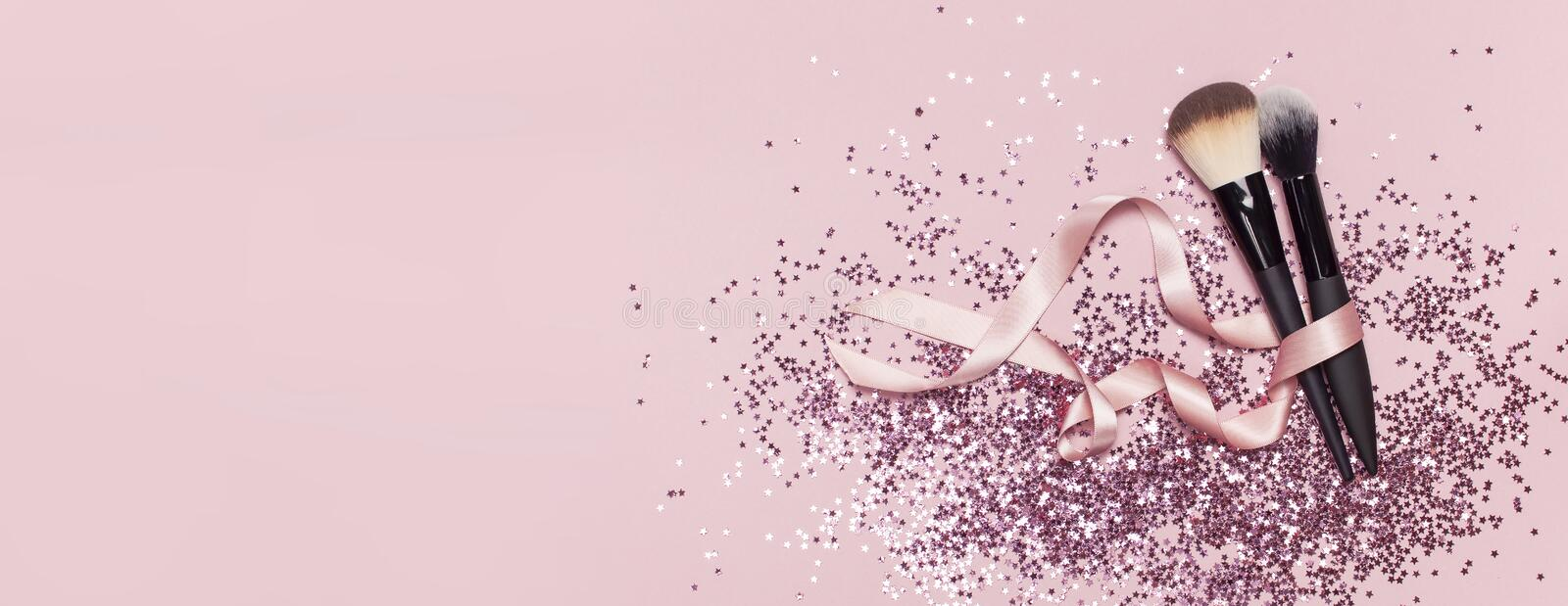 Two different Cosmetic makeup brushes with pink ribbon and holographic glitter confetti in the form of stars on pink background. Flat lay top view copyspace stock photography