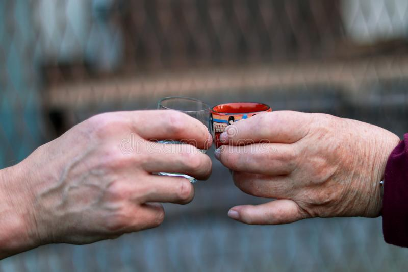 Two different people toasting to health and good harvesty in their lifes. Hands of woman and man are holding glasses of some royalty free stock photo