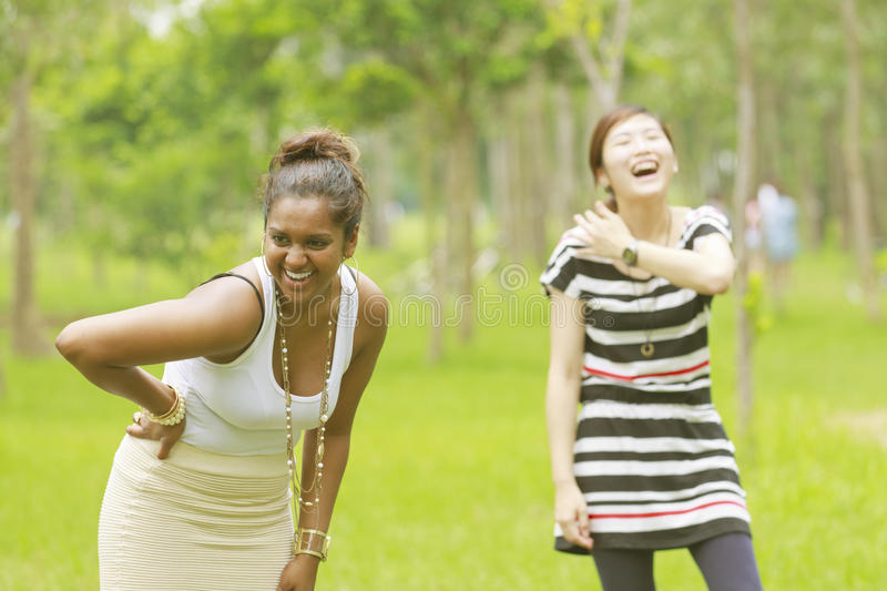 Two different races woman laughing stock photo