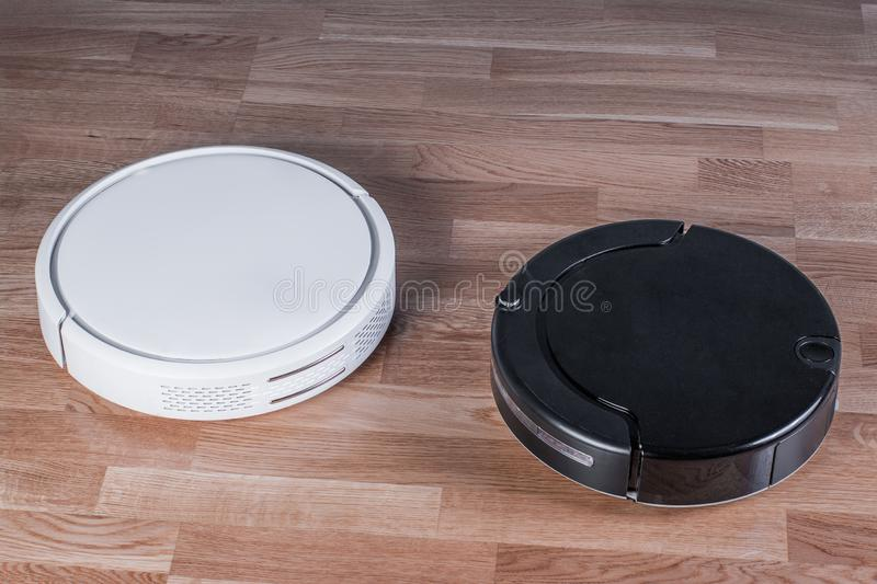 Two different Robotic vacuum cleaners, efficient dust absorption in absence of householder, modern smart appliance for cleaning. House royalty free stock image