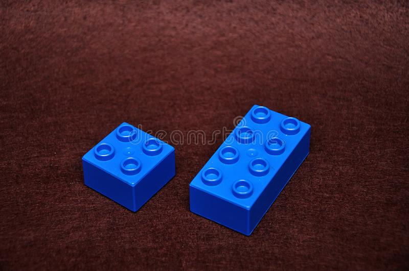 Two different size blue building blocks. On a brown background royalty free stock photo