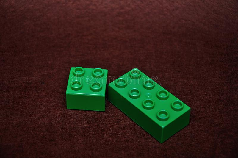 Two different size green building blocks. On a brown background stock photos