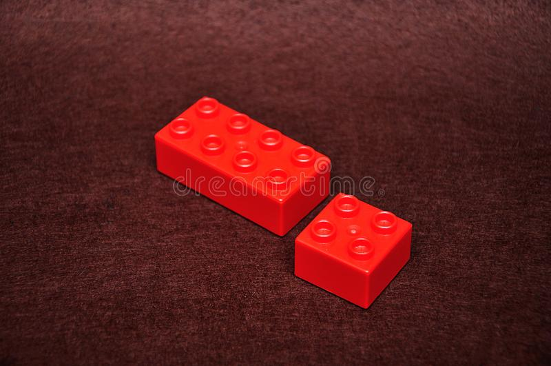 Two different size red building blocks. On a brown background stock image