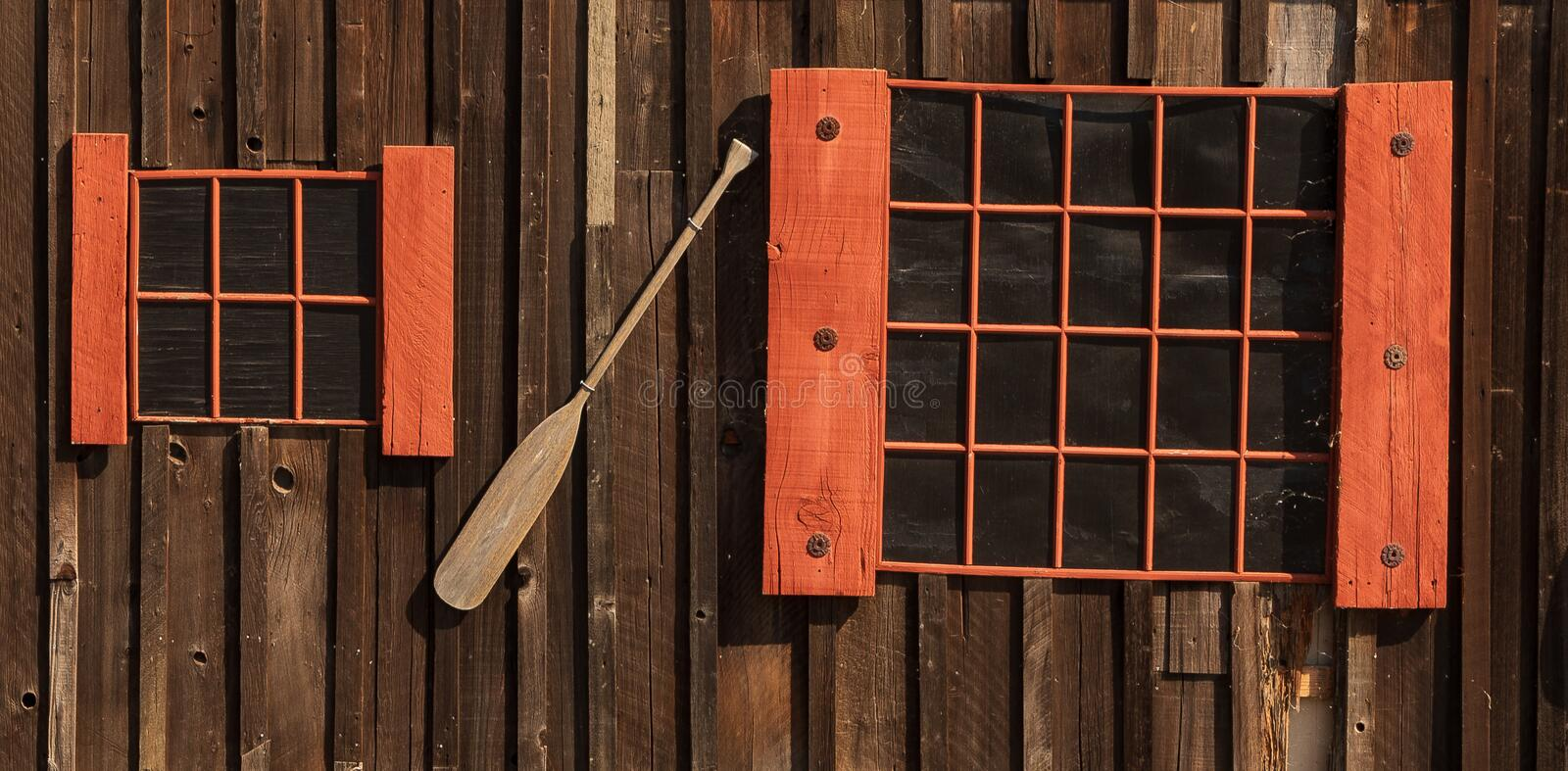 Two different size red framed windows with boat paddle on wall stock image
