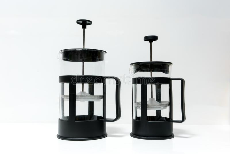Two different sizes of French press coffee maker on whi royalty free stock image