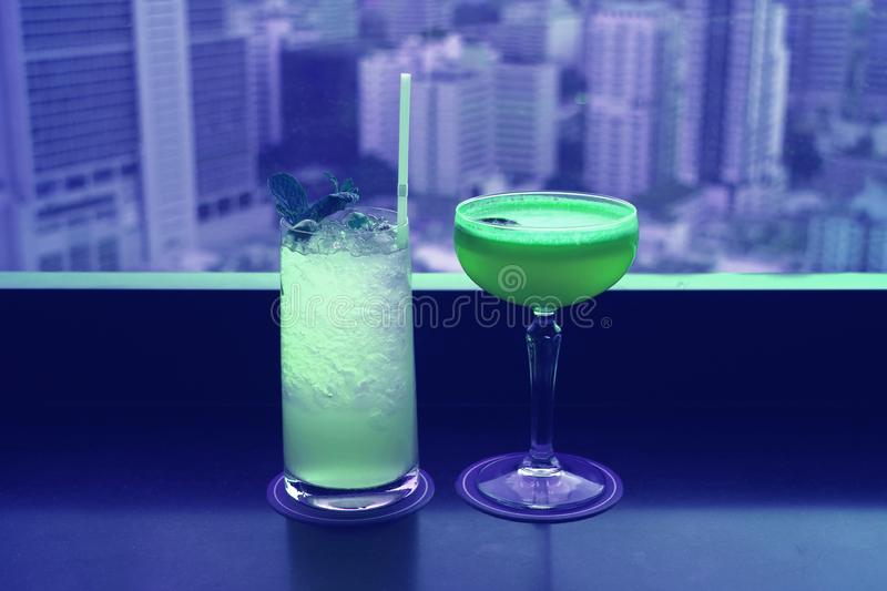 Two different type of cocktails in vibrant green color on the rooftop bar`s table with blurry skyscrapers view in background royalty free stock image