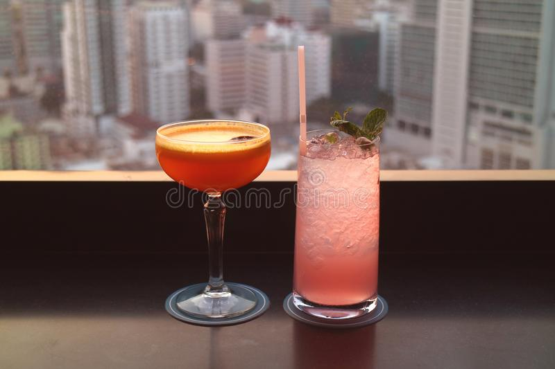 Two different type of juicy cocktails on a rooftop bar`s table with blurry skyscrapers view in the backdrop royalty free stock photography