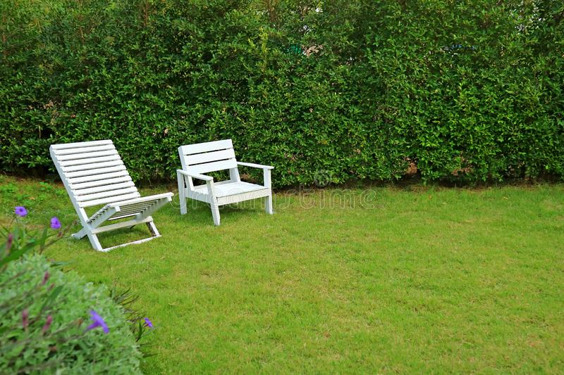 Two different type of white colored wooden chairs in vibrant green garden royalty free stock photography