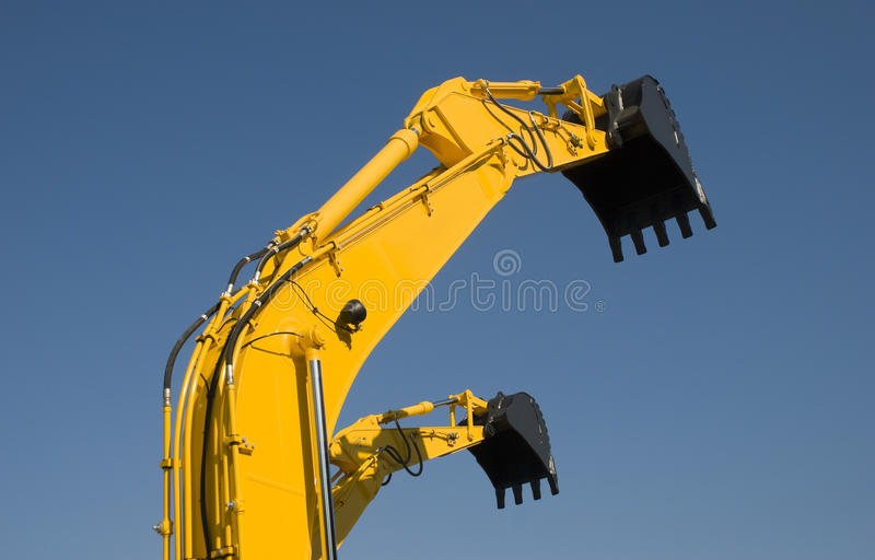 Two Digger. Two yellow digger isolated on blue sky stock images