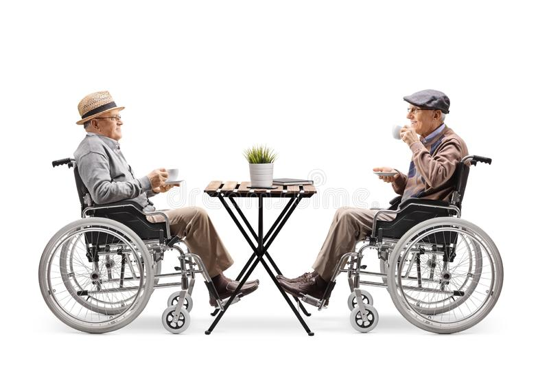 Two disabled elderly men in wheelchairs drinking coffee at a cafe. Full length profile shot of two disabled elderly men in wheelchairs drinking coffee at a cafe royalty free stock images