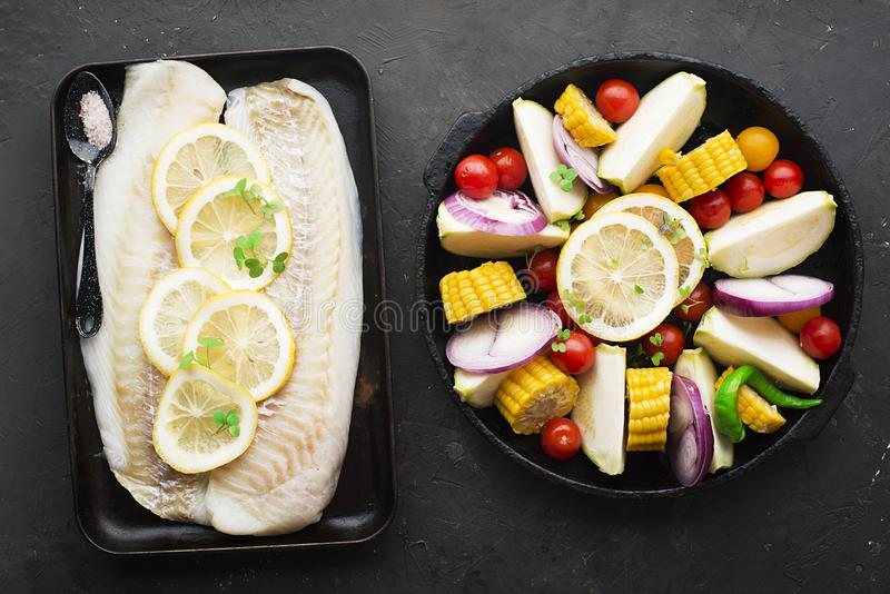 Two dishes before baking: cod with lemons and assorted organic garden vegetables in round form: corn, zucchini, onion stock photos