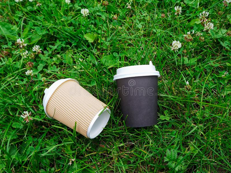 Two disposable paper coffee cups lie on the ground among the clover and green grass. stock image