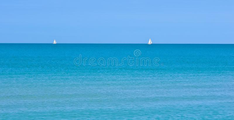 Two distant sailboats on a calm sea. Two distant sailboats on the horizon of a tropical sunny day with a breeze and no clouds on the Gulf of Mexico a calm sea stock images