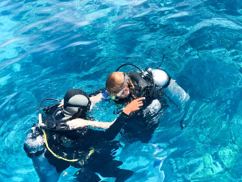 Two divers in black scuba diving suits, a man and a woman with oxygen bottles sink under the transparent blue water in the sea, th royalty free stock photography