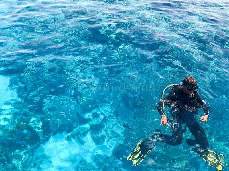 Two divers in black scuba diving suits, a man and a woman with oxygen bottles sink under the transparent blue water in the sea, th stock images