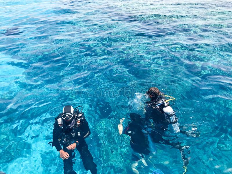 Two divers in black scuba diving suits, a man and a woman with oxygen bottles sink under the transparent blue water in the sea, th stock photos