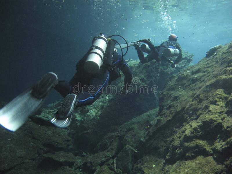 Two divers exploring the cenotes in Mexico - Underwater at cenote Chac Mool in the Riviera Maya, Mexico. Scuba divers underwater at cenote Chac Mool in the royalty free stock photo