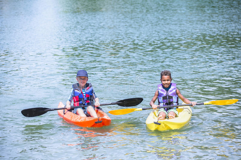 Two diverse boys kayaking together on the lake royalty free stock photos