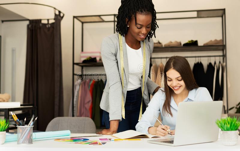 Two Diverse Dressmakers Creating New Fashionable Clothing Line In Studio stock photography