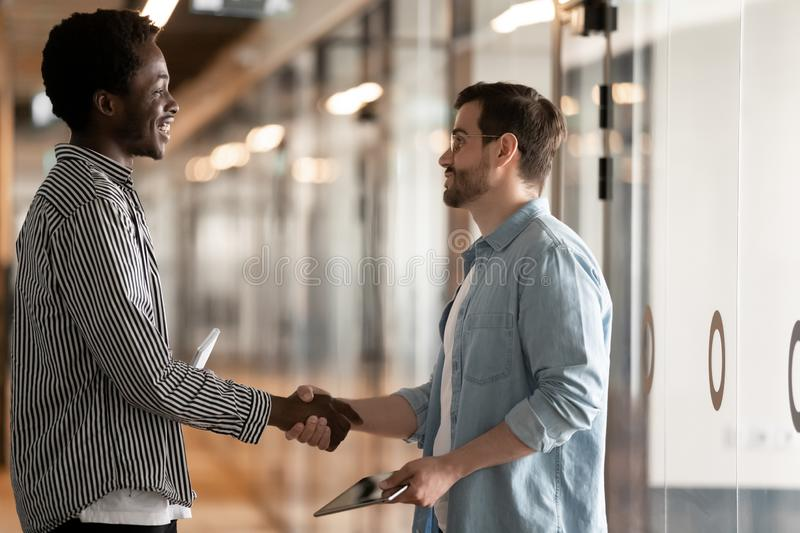 Two diverse male colleagues greeting handshaking standing in office hall. Two diverse male colleagues greeting handshaking talking standing in office hall stock images