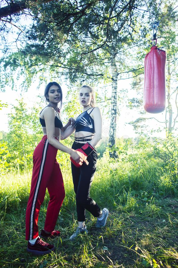 Two diverse nations girls fighting boxing outside in green park, sport summer people concept stock photos