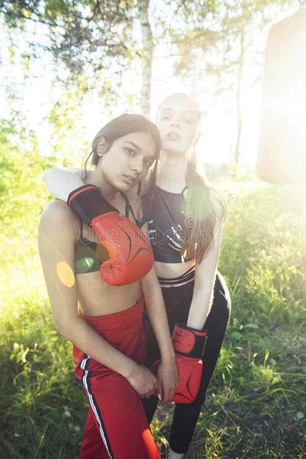 Two diverse nations girls fighting boxing outside in green park, sport summer people concept royalty free stock images