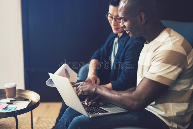 Two diverse office colleagues working together on a sofa royalty free stock photography