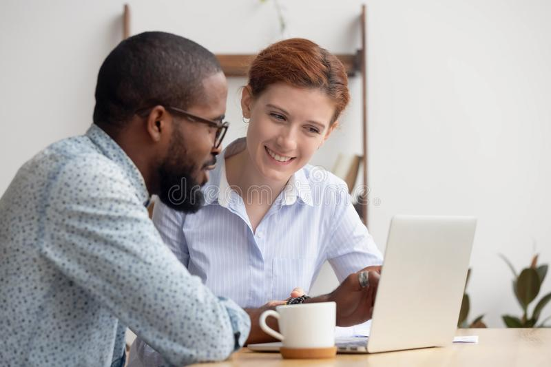 Two diverse smiling businesspeople discussing online project stock photography
