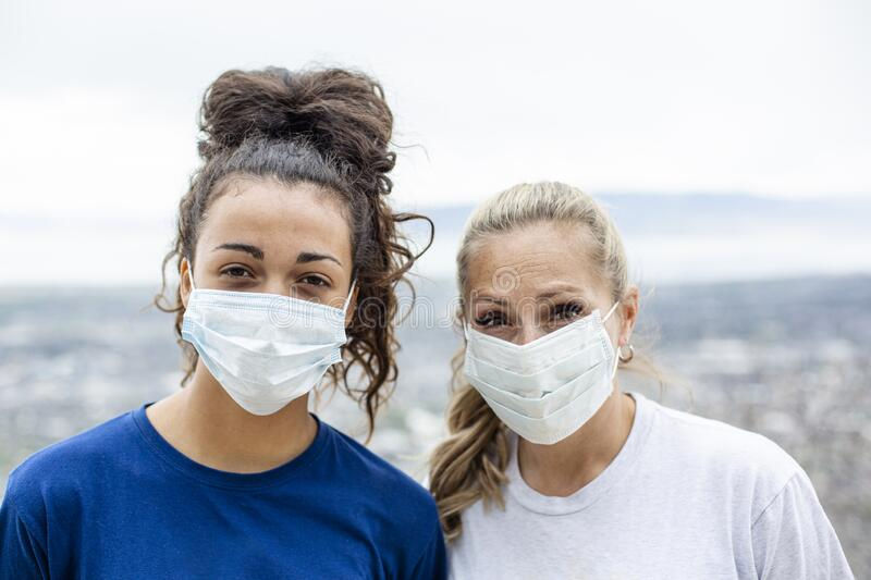 Two diverse women wearing personal protective equipment masks as they walk outdoors stock photo