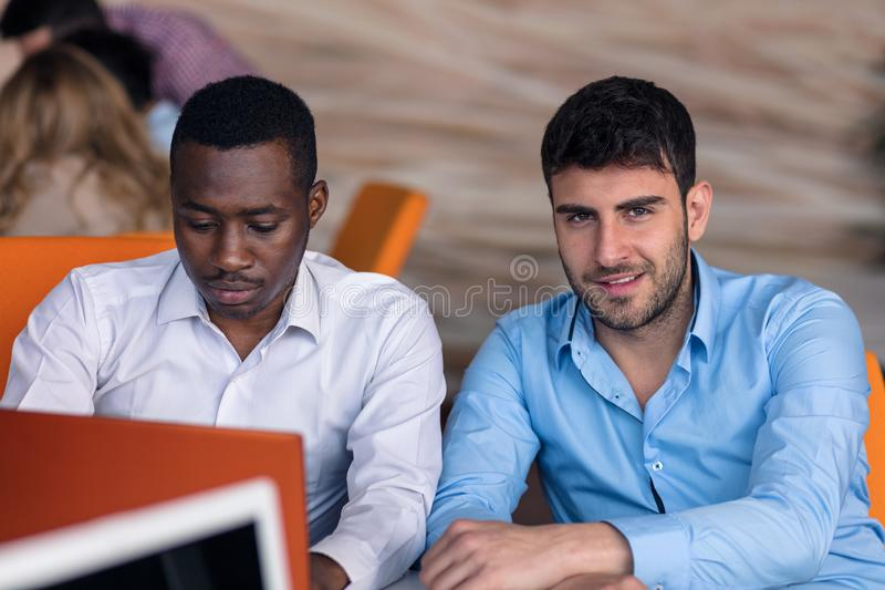 Two diverse work colleagues smiling while sitting together in an office discussing paperwork and working on a laptop stock images