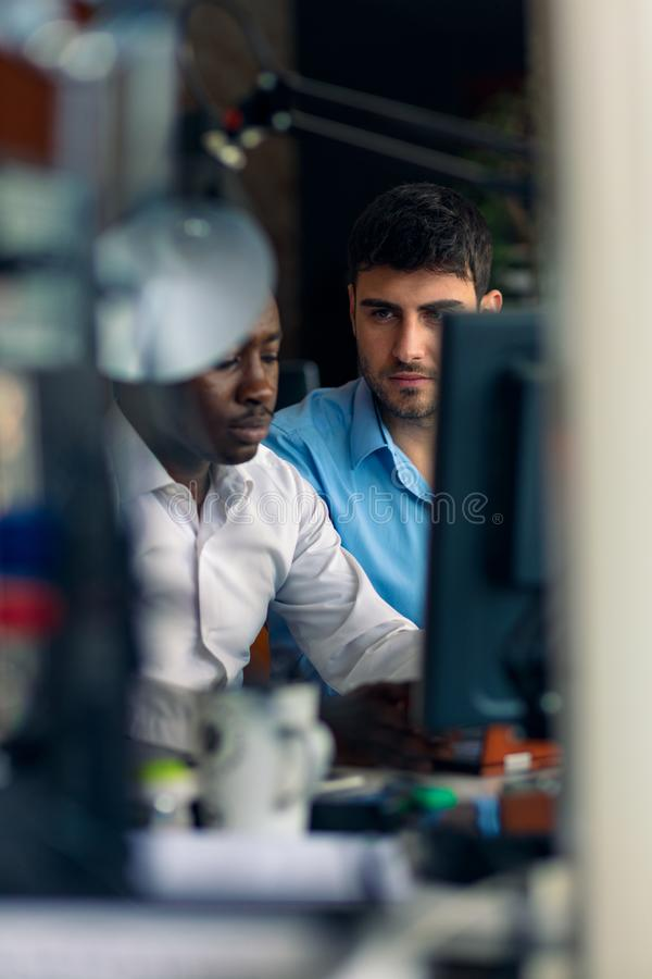 Two diverse work colleagues smiling while sitting together in an office discussing paperwork and working on a laptop stock photos