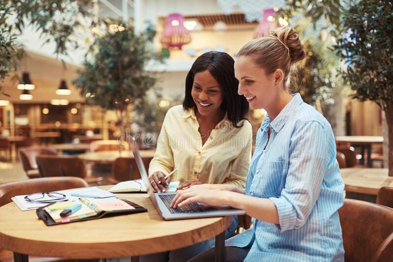 Smiling young businesswomen working together in an office lounge royalty free stock image
