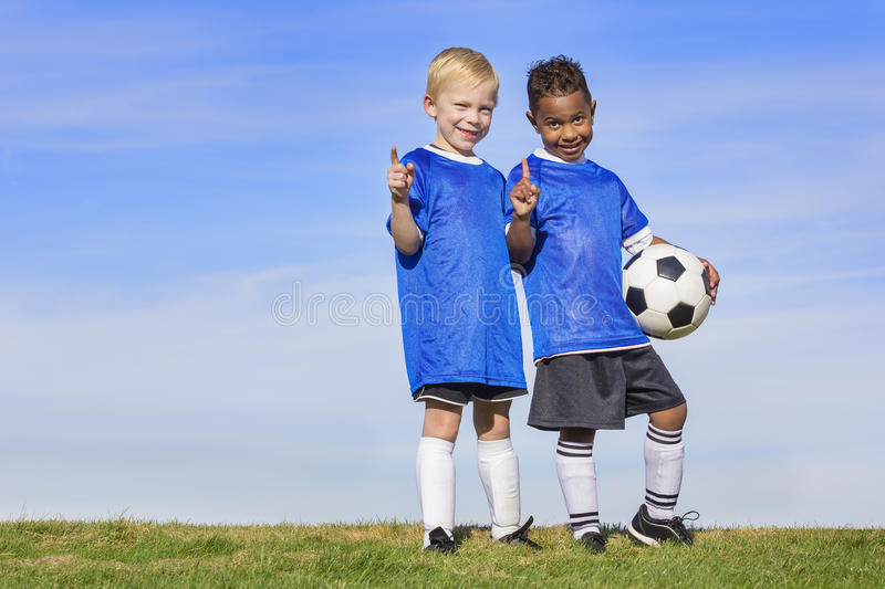 Two diverse young soccer players showing No. 1 sign. Full length view of two youth recreation league soccer players. Two diverse little boys standing on a grass stock photos