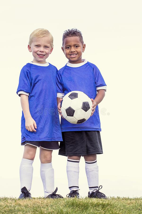 Two diverse young soccer players holding a soccer ball royalty free stock photo