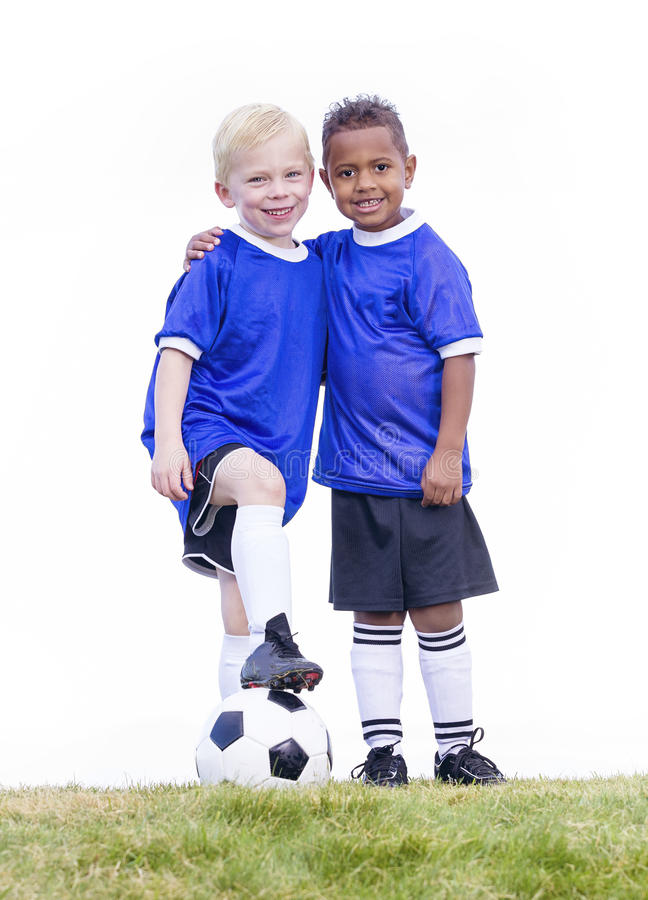 Two diverse young soccer players on white background. Full length view of two youth recreation league soccer players. Two diverse little boys standing on a grass stock image