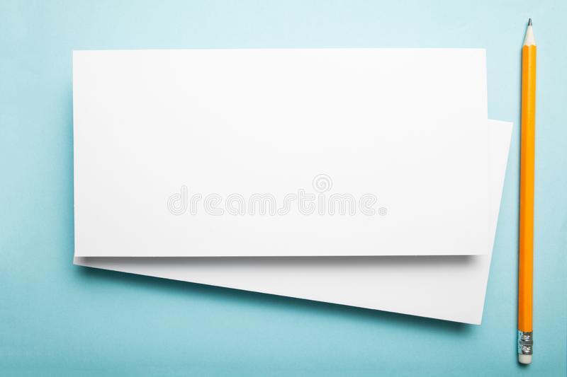 Two DL flyers on a blue background with a pencil.  royalty free stock photos