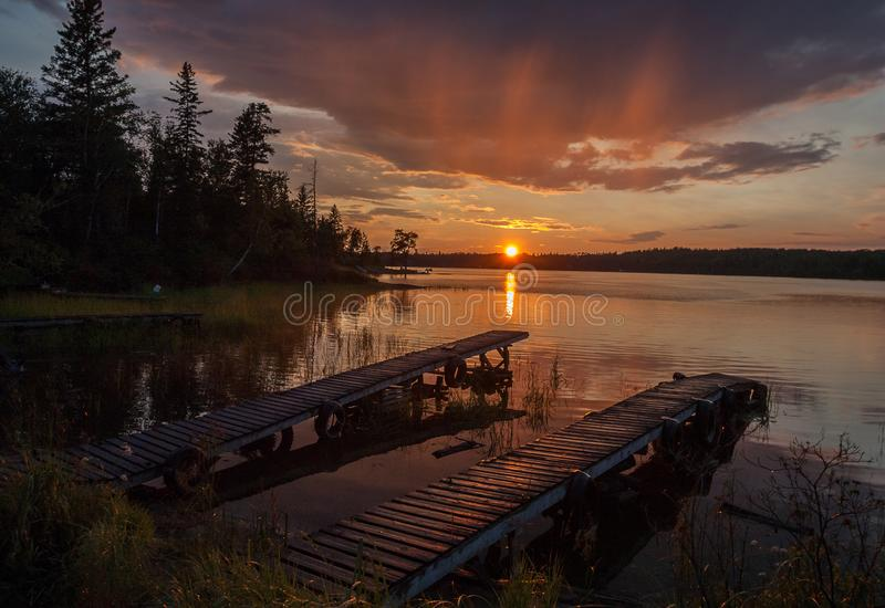 Two docks in sunset over lake stock image