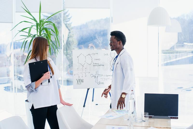 Two doctors communicate at the conference room in the hospital. African male and caucasian female medical students at. Two young doctors communicate at the stock photo