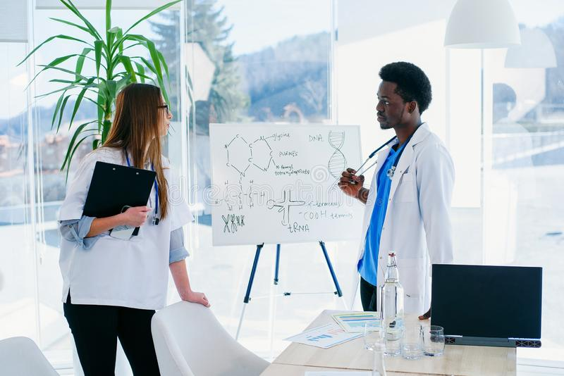 Two doctors communicate at the conference room in the hospital. African male and caucasian female medical students at. Two young doctors communicate at the stock image
